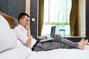 Businessman in hotel room working with laptop.